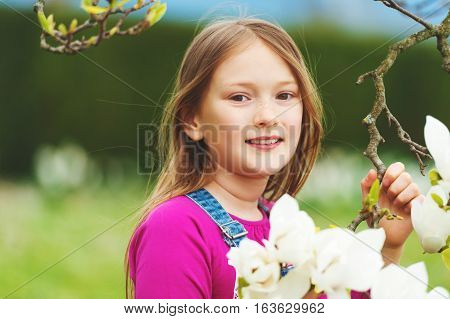 Spring portrait of 7-8 year old pretty little girl with magnolia flowers