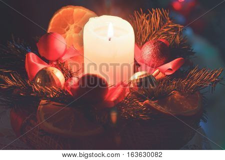 lit candle evening new year christmas wreath red balls