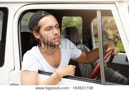 Handsome Young Unshaven Man Wearing Casual T-shirt And Baseball Cap Backwards Looking Out Of Open Wi