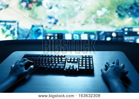 Man playing computer games online at home