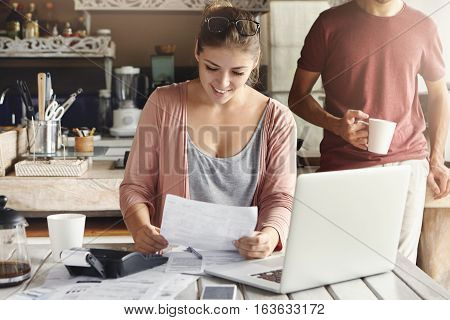 Young Pretty Woman Wearing Glasses On Her Head Smiling Happily While Reading Document Saying That Ba