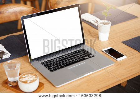 Business technology and communication concept. Minimalistic workspace with modern laptop computer with white blank screen generic mobile phone coffee and glass of water on wooden desk. Mock up poster