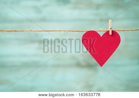 Paper heart hanging on twine against blue wooden texture for Valentines or Mothers day. Vintage toned.