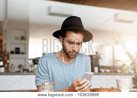 Handsome Young Man With Beard Checking Newsfeed Via Social Networks And Listening To New Tracks Onli