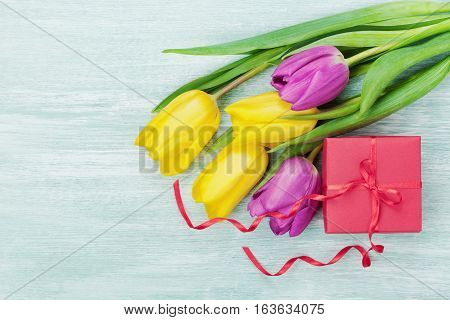Gift box and tulip flowers on rustic table for March 8 International Womens day, Birthday or Mothers day. Beautiful spring card, flat lay.