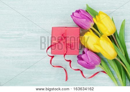 Gift box and tulip flowers on rustic table for March 8 International Womens, Birthday or Mothers day. Flat lay.