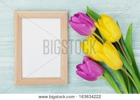 Empty frame and tulip flowers on rustic table for March 8 International Womens, Mothers or Birthday day. Beautiful spring card. Flat lay.
