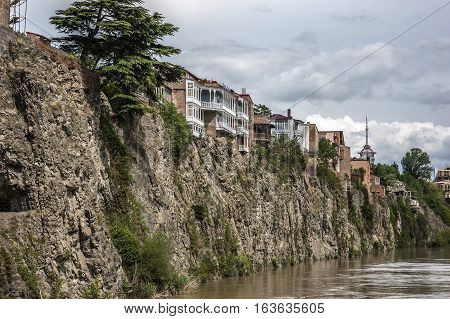Georgia Tbilisi. View on Avlabari district houses on a cliff leaving the water in the Kura River .