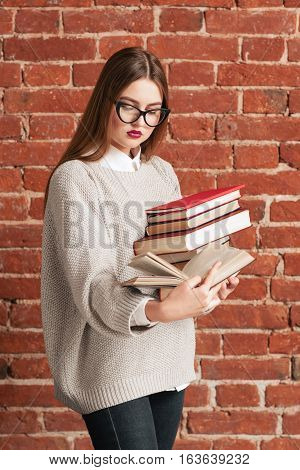 Busy girl student reading while walking. Smart girl going to prepare for exam with bunch of books, brick background. Education, hobby, literature, study, reading concept