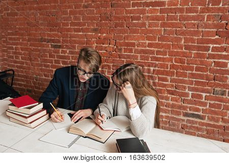 Side view on two learning students free space. Young man and woman studying in library, preparing for exams. Education, study, teamwork, brainstorm concept