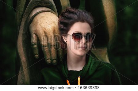 Beautiful woman with heart-shaped glasses and a big wooden statue's hand on her shoulder
