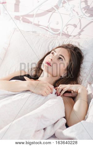 Beautiful thoughtful girl lying in bed, free space. Young woman dreaming in morning after awaking. Good dream, pensive mood, romantic, pleasure, memories concept