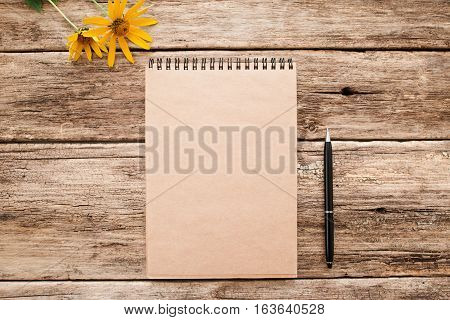 Brown sketchbook on old wood flat lay mockup. Top view on vintage notebook with pen and bright yellow flowers on grunge wooden background. Art, inspiration, imagination, planning concept