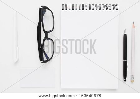 Blank notebook with stationery and glasses flat lay mockup. Top view on writer with bad vision work tools, free space. Art, business, creation, imagination, stationery, workplace, orderliness concept