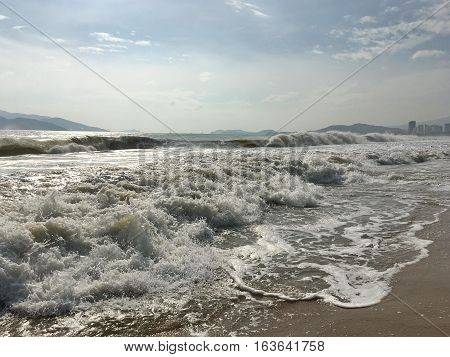 Waves splashing on the beach in the morning, the rays of the sun glisten on the sea water, wave after wave runs ashore, on the horizon of low mountains, sky with clouds