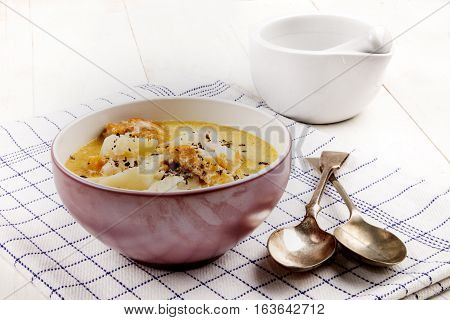 fish soup with smoked haddock potato and crushed peppercorn in a bowl