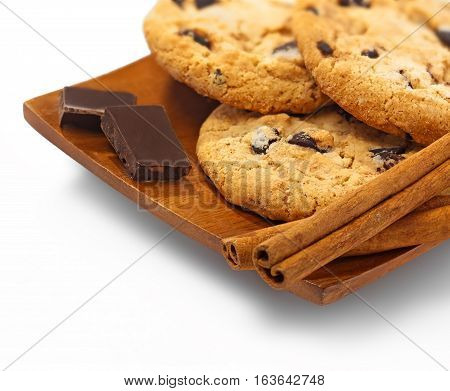 Cookies chocolate and cinnamon sticks on the wooden plate isolated whote background