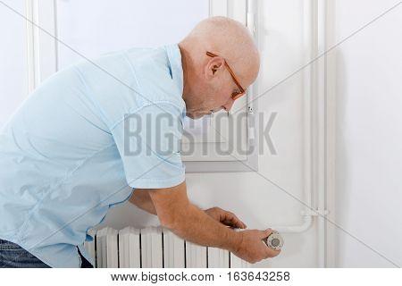 handsome mature man changing temperature of radiator