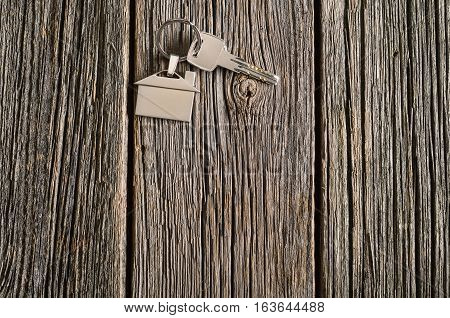 Home, real-estate or property concept with silver keys with house symbol on old wooden floor background. Blank concept frame with copy space