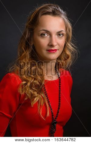 The young magnificent woman in an elegant dress of scarlet color with beautiful ringlets and a black beads