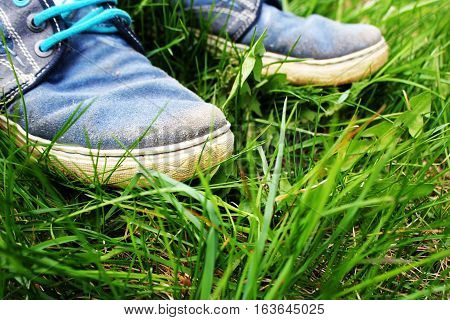 Travel background. Old shoes on grass .