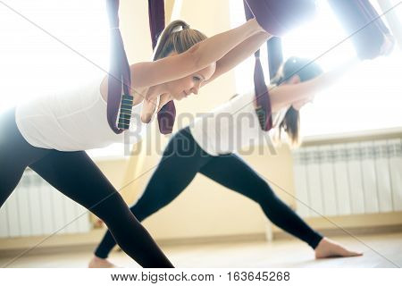 Two young yogi women doing aerial yoga practice in purple hammocks in fitness club. Beautiful females working out in class, performing aero yoga. Variation of Parsvottanasana, Pyramid pose
