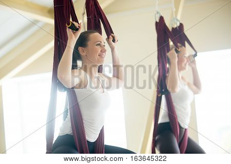 Two young yogi women doing aerial yoga practice in purple hammocks in fitness club. Beautiful females working out, performing aero yoga in class. Variation of baddha konasana, cobbler, butterfly pose