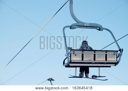 A snowboarder sitting on the chairlift with a blue sky