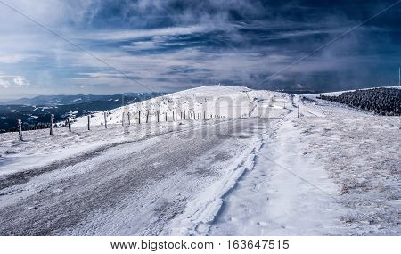 winter hiking trail with nice sky and snow near Pretulalpe hill in Stuhleck mountain ridge in Fischbacher Alpen mountains in Styria
