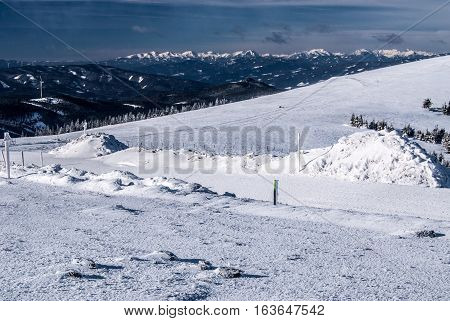 winter austrian alps panorama with Hochschwab, Seckau Tauern and Ennstal Alps from Pretulalpe hill in Fischbach Alps in Styria with snow and blue sky with clouds