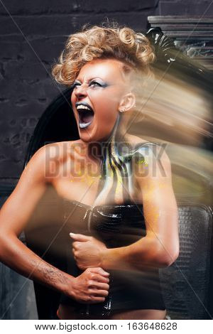Portrait of screaming punk woman long exposure. Rocker girl with bright body art, make up and hairstyle, get away her pain. Distress, body art, aggression, lifestyle, psychotherapy concept