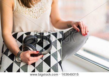 Beautiful woman sitting and daydreaming by the window