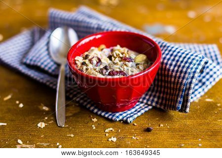 Healthy homemade granola or muesli with oats, dried pears, raisin, almonds, hazelnuts and honey in a red bowl for breakfast on a wooden table, selective focus