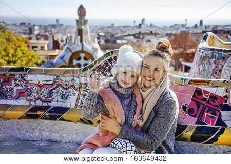 Mother And Child In Barcelona Handwaving While Sitting On Bench