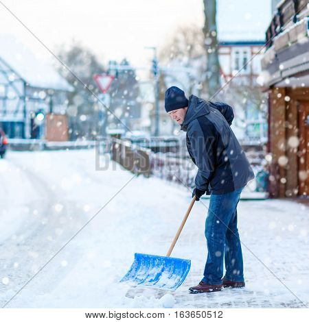 Man with snow shovel cleans sidewalks in winter. Winter time in Europe. Young man in warm winter clothes