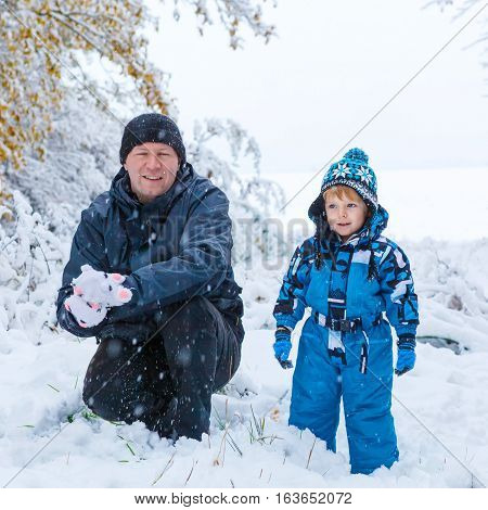 Winter portrait of kid boy and father in colorful clothes, outdoors during snowfall. Active outoors leisure with children in winter on cold snowy days. Happy man and son having fun with snow in forest