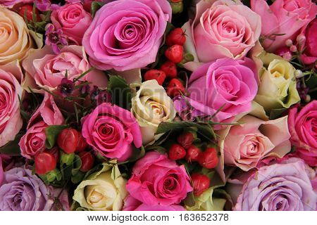 Various shades of pink roses in a wedding centerpiece