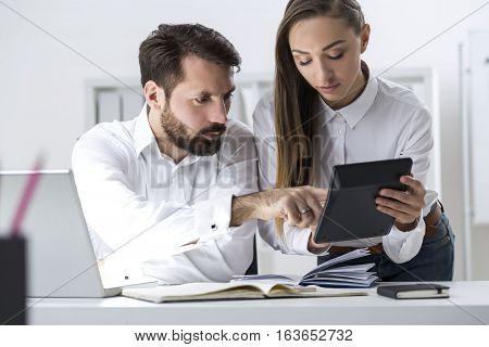 Boss And Secretary Looking At Calculator