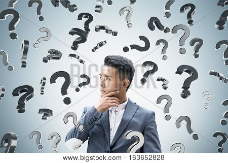 Close up of an Asian businessman thinking about his challenging problem while standing near a gray wall