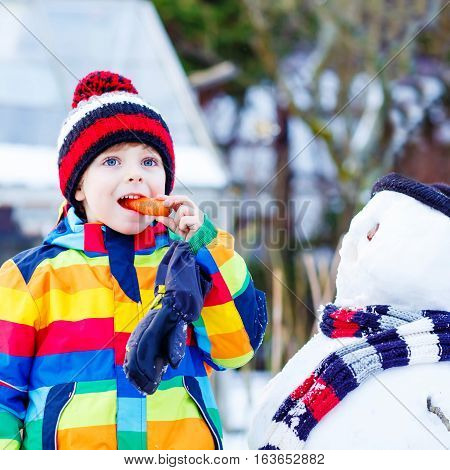 Adorable little kid boy making a snowman and eating carrot. child playing and having fun with snow on cold day. Active outdoors leisure with kids in winter.