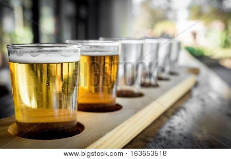 Beer samplers in small glasses individually placed in holes fashioned into a unique wooden tray. Focus is on the backlit front sample.