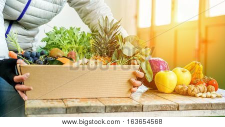 Fruit seller woman with different fruits and vegetables in shop - Worker preparing fruit ecological paper basket - Vegetarian and vegan concept - Focus on pineapple kiwi grapefruit - Warm filter