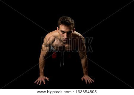 Muscular man making pushups in studio isolated on black background