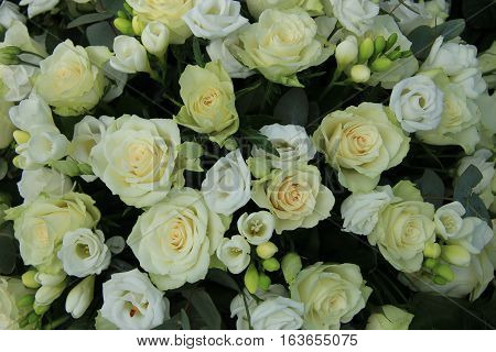 Freesias and roses in a white bridal arrangement