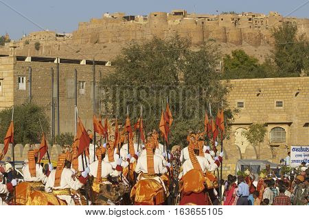 JAISALMER, INDIA - FEBRUARY 19, 2008: Camels and riders of the Indian Border Security Force lead a procession through the historic quarter during the Desert Festival in Jaisalmer, Rajasthan, India.