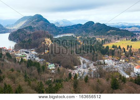 Hohenschwangau Castle Schloss aerial view with town, lake and bavarian alps mountain view, Fussen, Bavaria, Germany