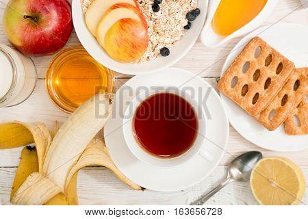 Healthy Breakfast. Muesli, Cup Of Tea, Honey, Cookies, Apple And Banana On White Table.