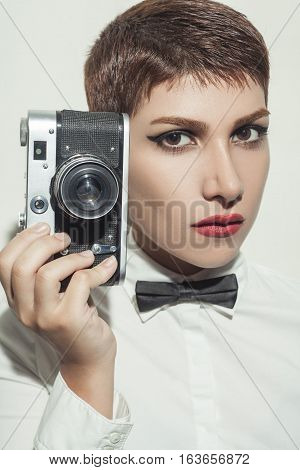 young beautiful woman photographer with camera and short hair style and classic wear with bow tie.
