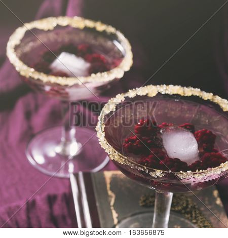 Two aperitif alcohol cocktails drinks with berries on purple background for romantic date. Square