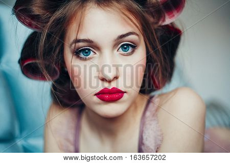 Beautiful young woman wearing curlers. Professional make-up and hairstyle. Perfect skin. Fashion photo.